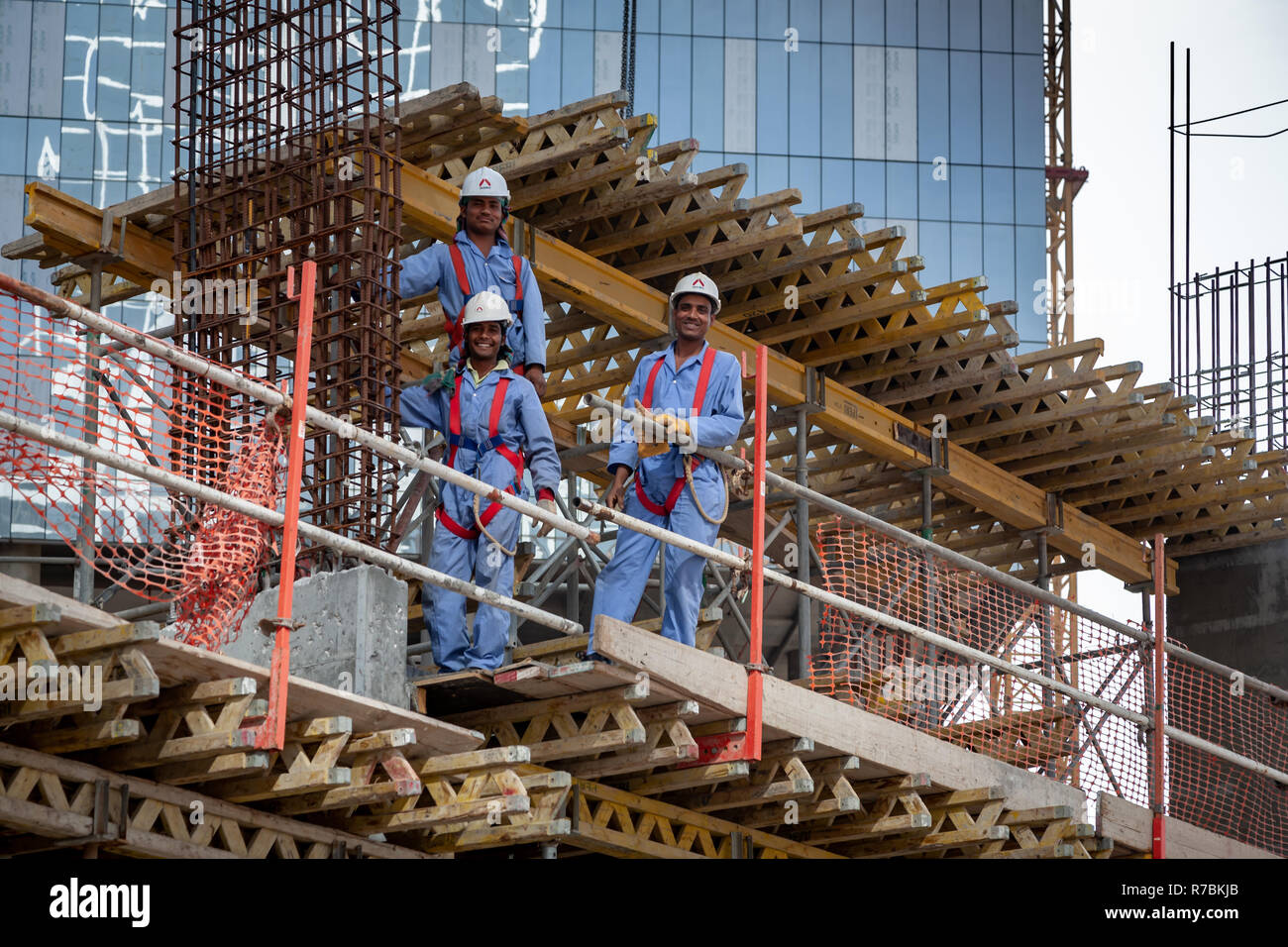 Three building workers up on scaffold on building site in Dubai - Stock Image