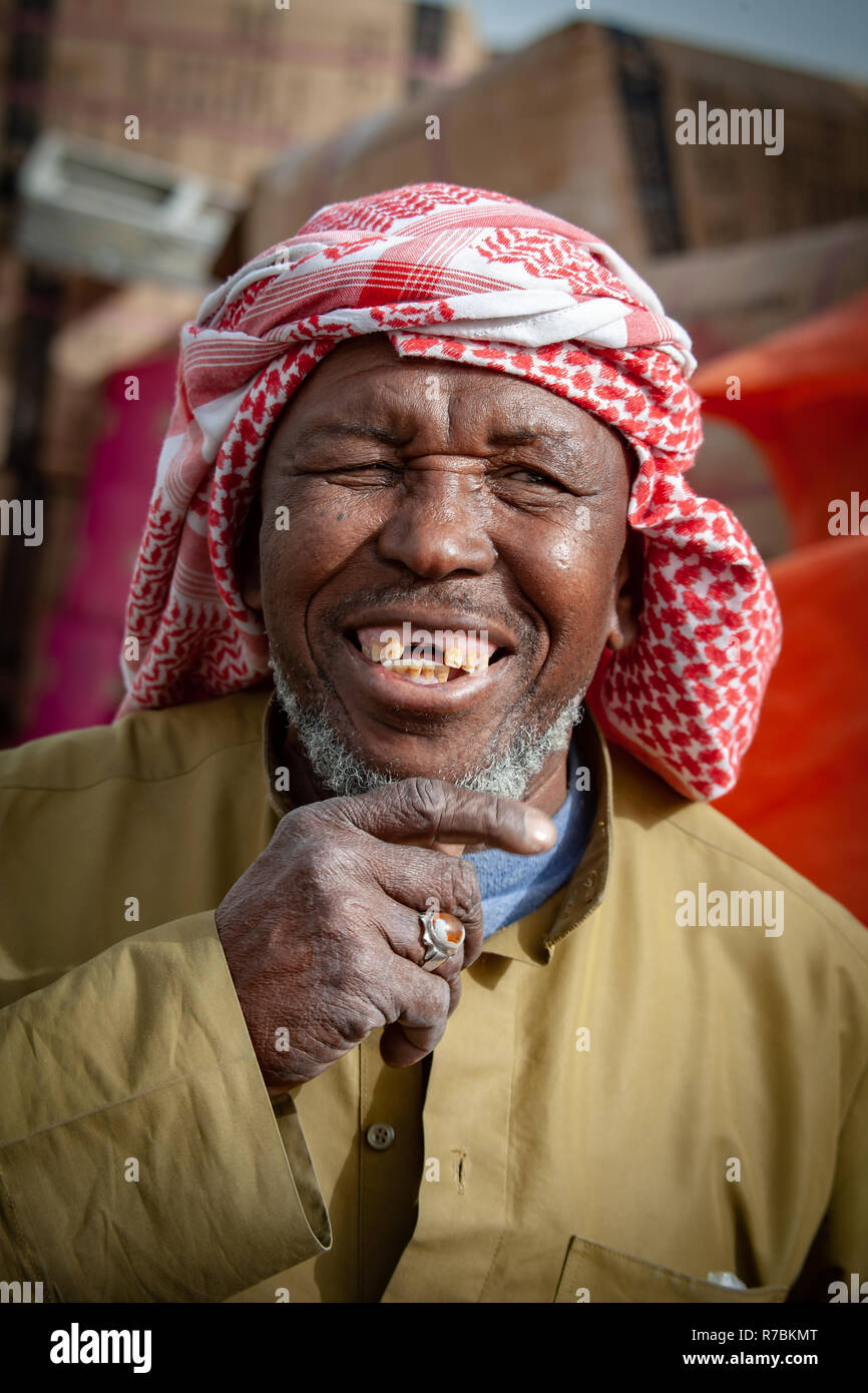 ghutra headdress wearing Smiling Market trader with missing teeth in a Dubai Souk - Stock Image