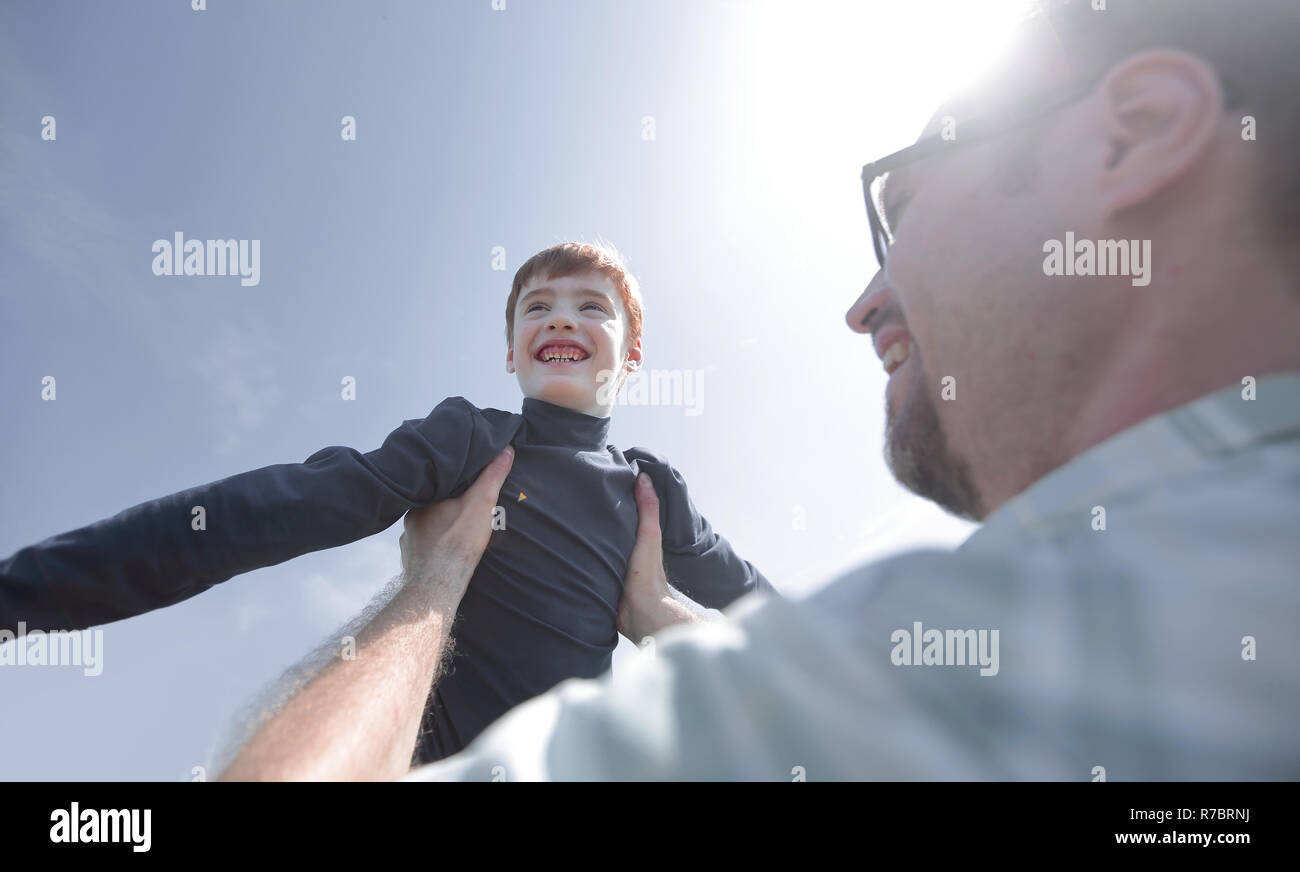 stylized photo.a happy father holds his son in his hands - Stock Image