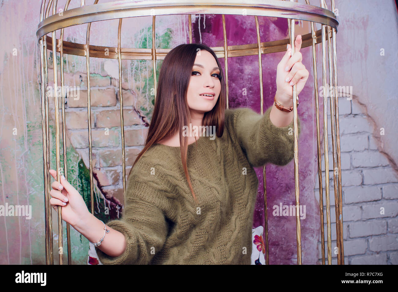 Beautiful girl in green sweater is sitting on big cozy carpet and holding boxes of gifts for her beloved. On the back there are a white fireplace covered sits in a cage - Stock Image