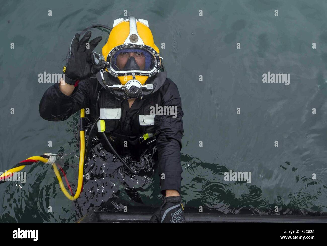 U.S. Navy Equipment Operator 3rd Class Thomas Dahlke, Underwater Construction Team 2, enters the water during an underwater surface-supply dive in support of Balikatan 2017 at Ipil Port in Ormoc City, Leyte, May 12, 2017. The surface-supply dive training prepares Philippine and U.S. service members to clear debris in ports and open up supply lines for victims of natural disasters and crises. Stock Photo