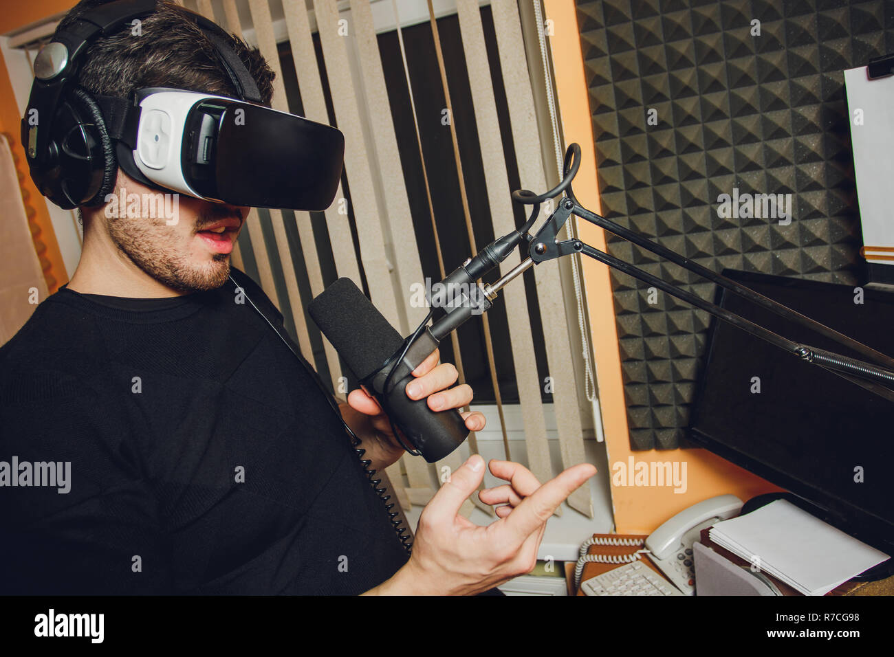 Portrait of bearded male in a suit with virtual reality glasses on his head isolated on grey background. - Stock Image