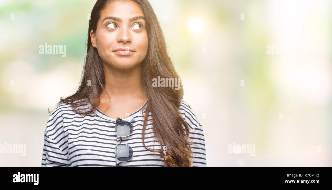 Young beautiful arab woman wearing sunglasses over isolated background smiling looking side and staring away thinking. Stock Photo