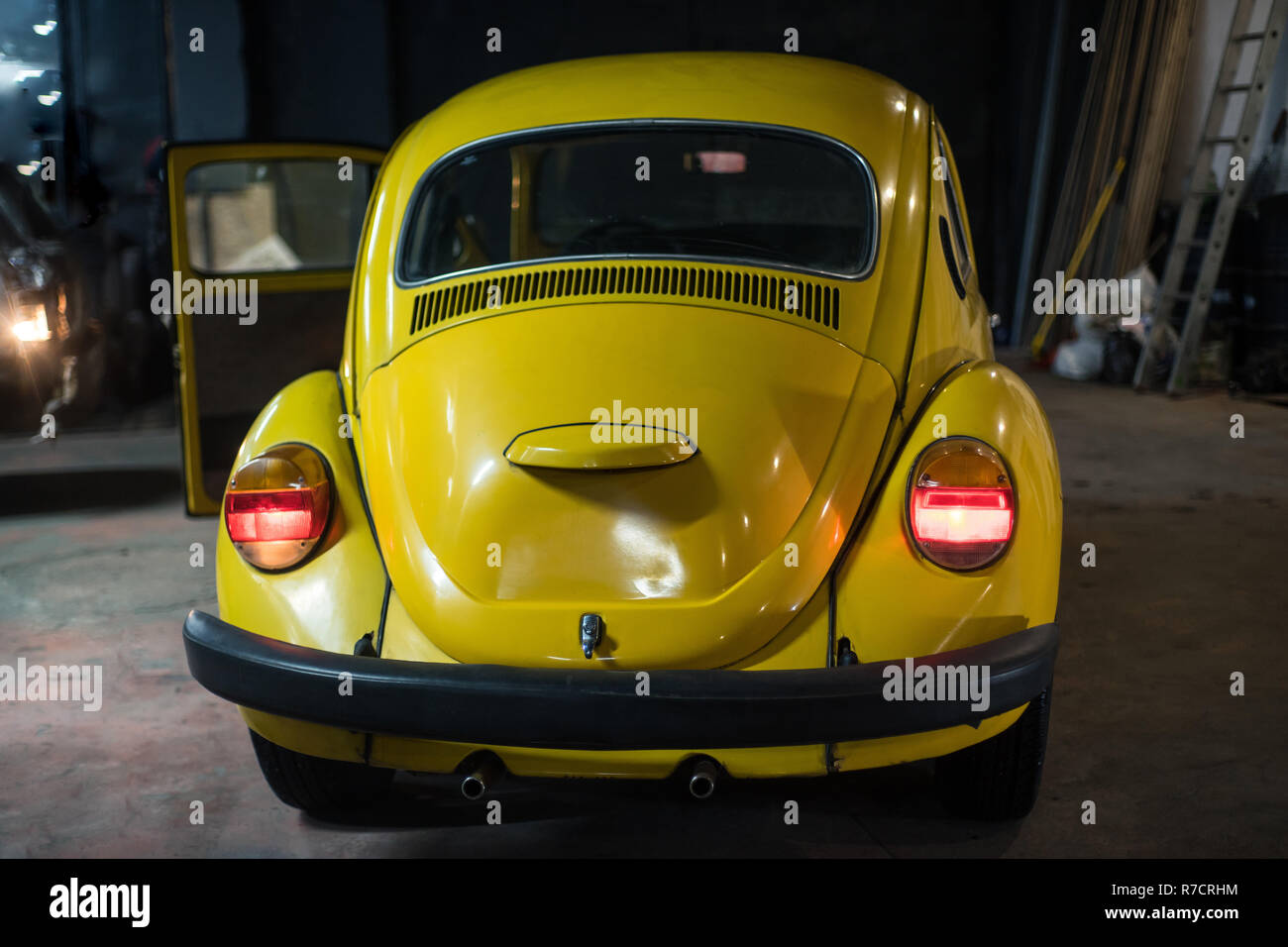 Close up of yellow classic car in workshop interior - Stock Image