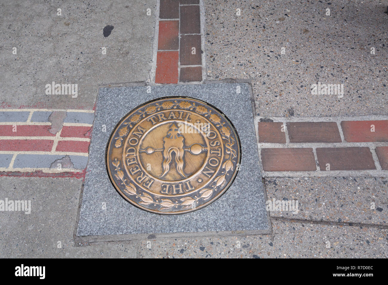 A brick line and brass medallion in the pavement marking the historic Freedom Trail in Boston, MA - Stock Image