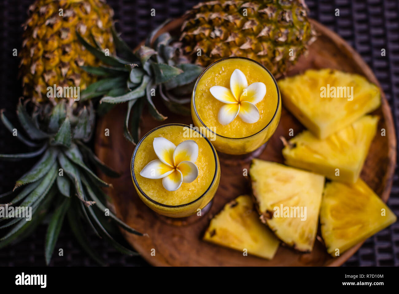 Two Glasses Of Fresh Pineapple Juice Decorated With Plumeria Flowers