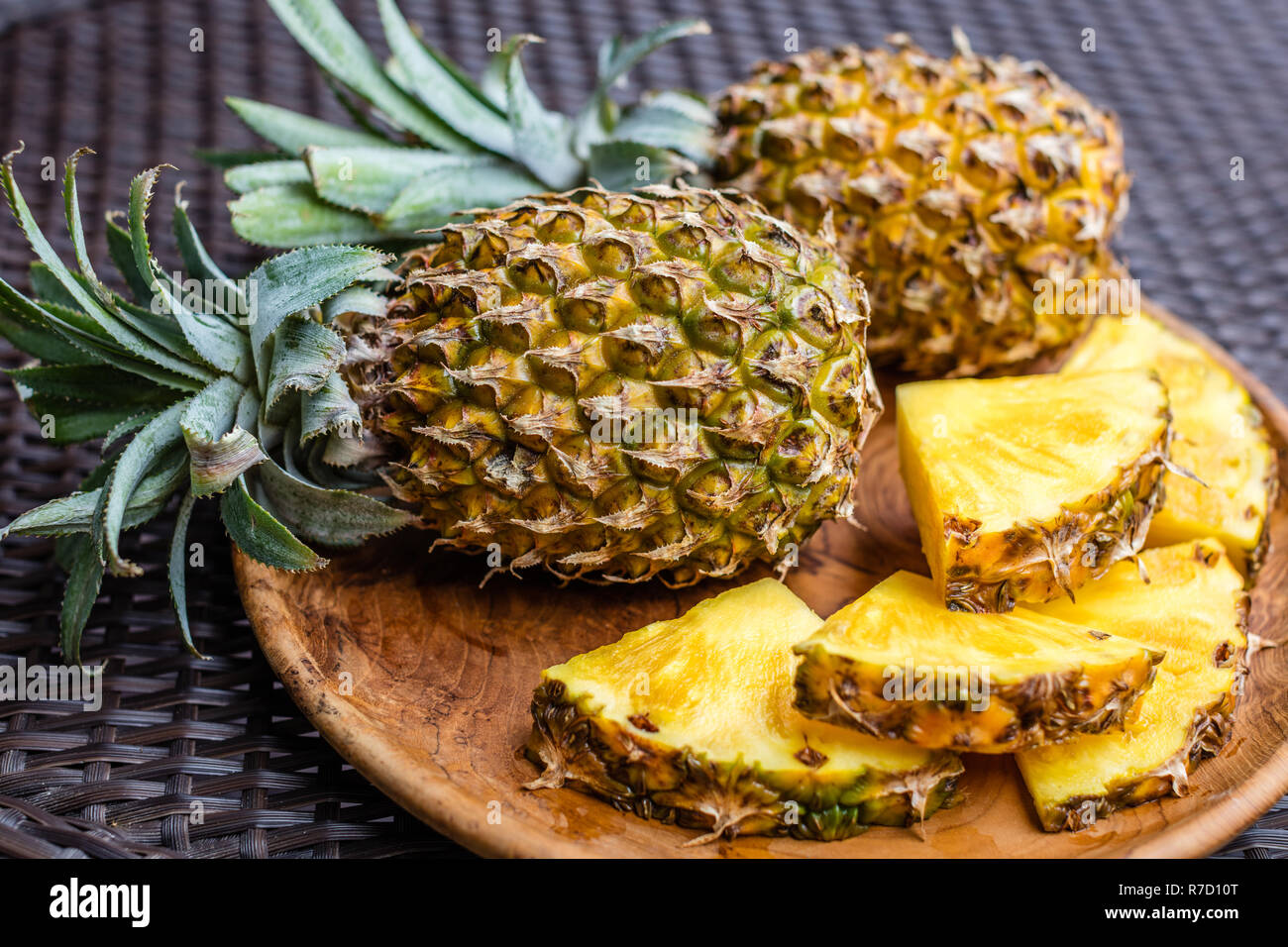 Two Whole Pineapples And Big Cut Pieces On A Round Wooden Tray Over