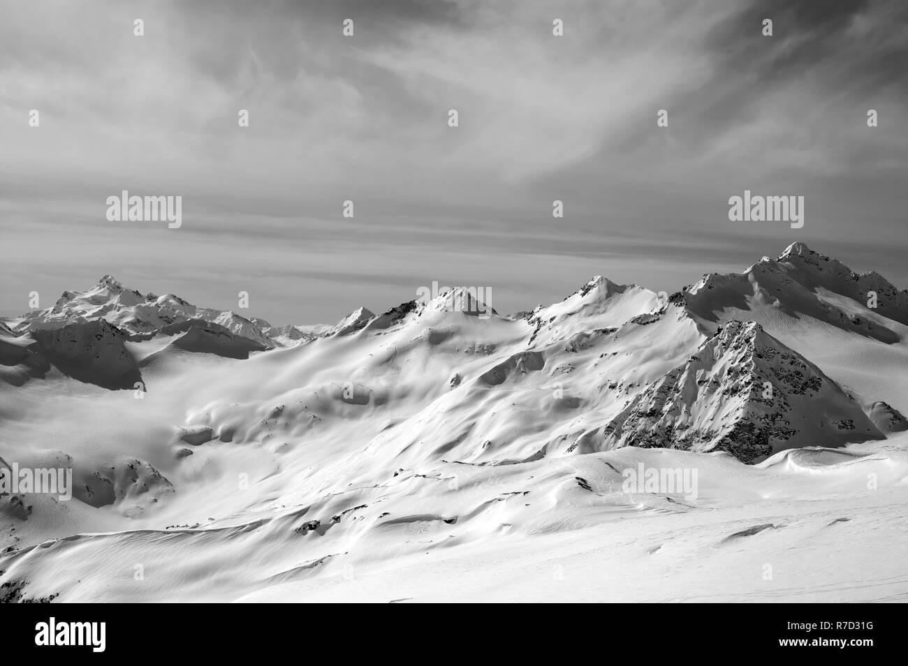 Black and white view on snowy mountain peaks and off-piste slope at sun evening. Caucasus Mountains in winter, Elbrus region. - Stock Image