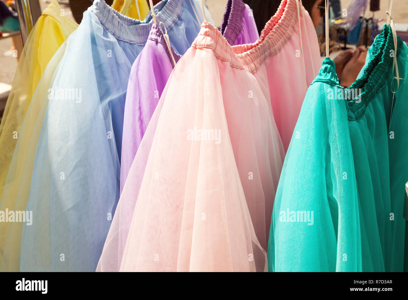 Row of hanging colorful gauze skirts at a clothing store. Brightly colored performance costumes background - Stock Image