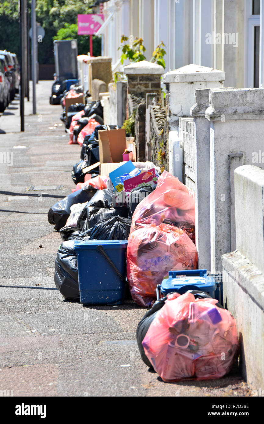 Street scene pavement waste management applied to terraced houses with rubbish bags & bins outside for refuse collection by council Southend Essex UK - Stock Image