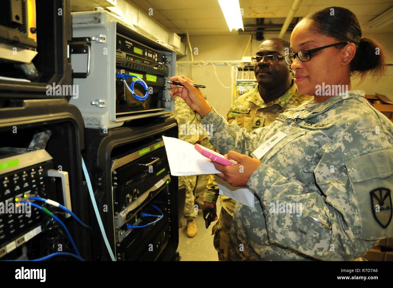 Spc. Brooke Ramsden, an information technology specialist, Joint Force Headquarters, Virgin Islands National Guard, troubleshoots the Joint Incident Site Communications Capability while Sgt. 1st Class Ofari Benjamin, communications lead, guides her during Vigilant Guard 17-03 in St. Thomas, May 16. Members of the J6 Information Management Branch supported the mission in terms of all computer communication-data, and telecom or telephone capabilities. Stock Photo