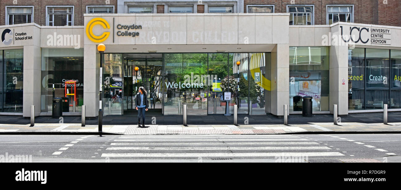 A person beside Belisha beacon & Pedestrian crossing outside entrance & welcome sign at Croydon College campus education buildings London England UK - Stock Image