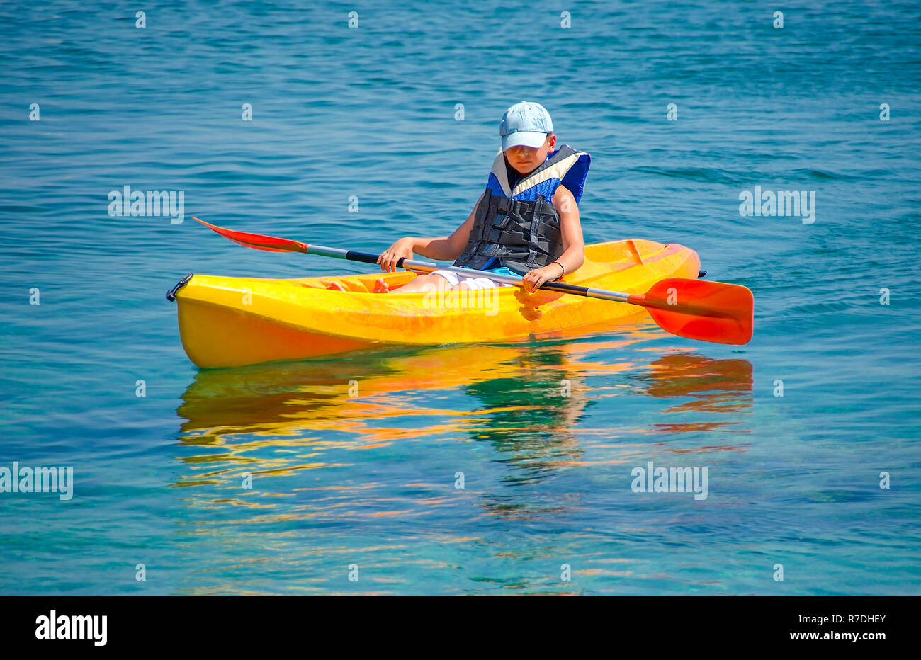First kayaking lessons. Boy with blue hat and life buoy suit in kayak lessons during summer vacations in an island of Greece - Stock Image