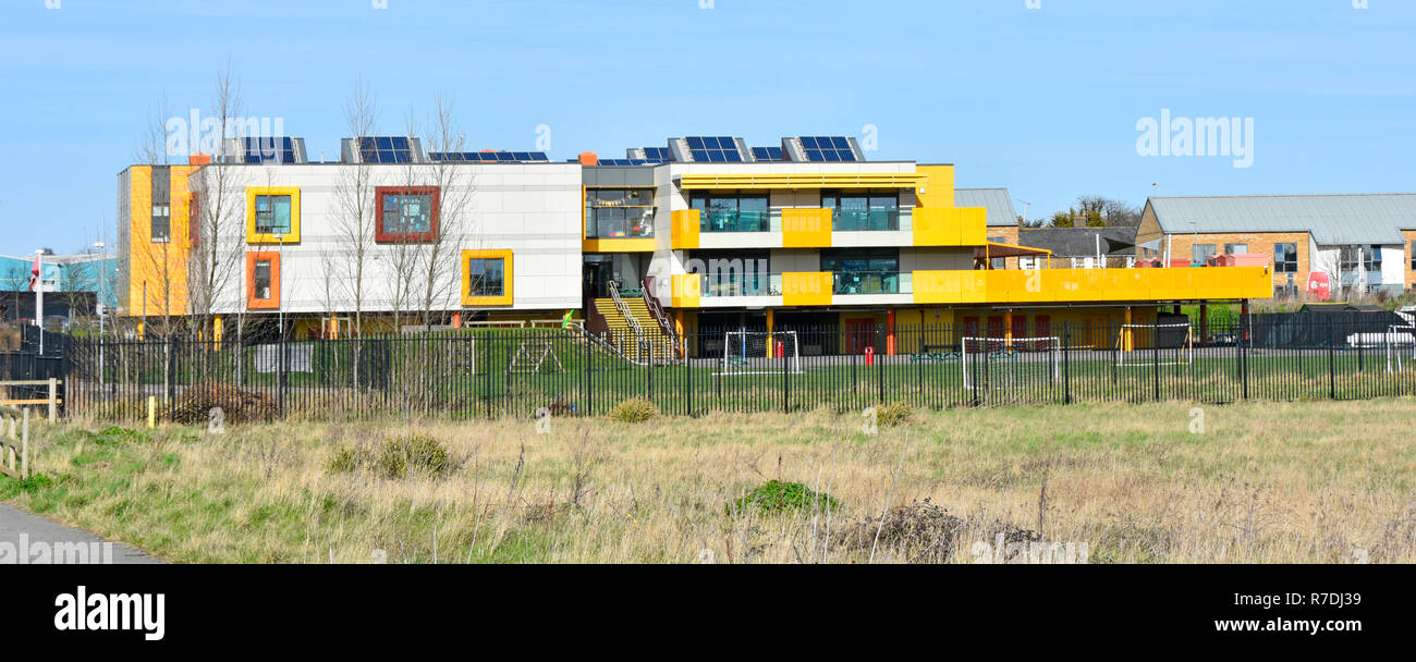 New modern 2012 colourful primary school education building & play area close to Shoebury Garrison housing development Shoeburyness Southend Essex UK - Stock Image