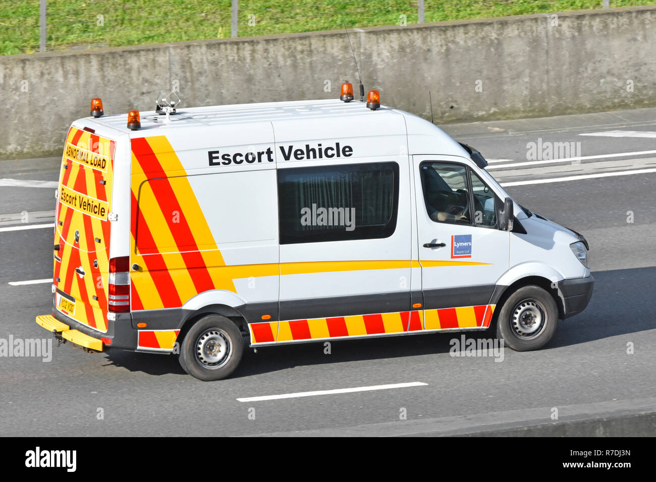 Specialist high visibility abnormal & wide load escort vehicle service by Lymers Assist freight road transport business van driving on UK m25 motorway - Stock Image