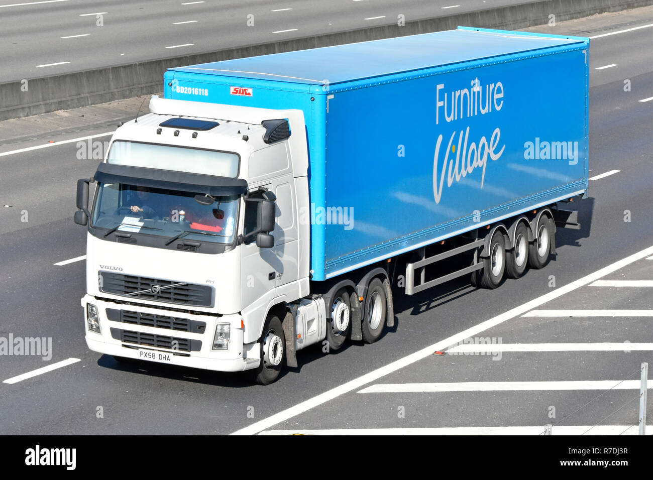 White hgv juggernaut lorry truck driver & blue Furniture Village articulated supply chain transportation trailer driving along motorway England UK - Stock Image