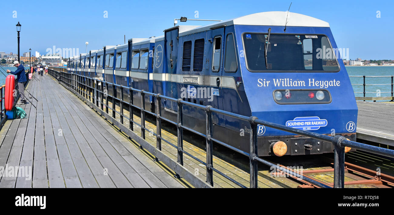 Famous Thames Estuary Southend Pier public transport railway & train returning to distant Southend on Sea coastline seaside resort Essex England UK - Stock Image