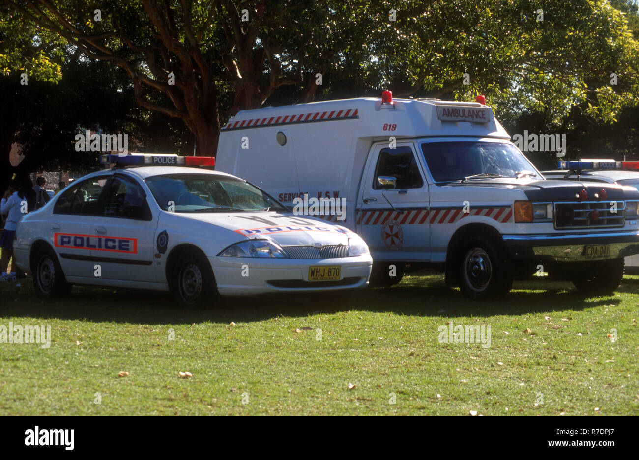 PARKED EMERGENCY SERVICES VEHICLES, NEW SOUTH WALES AMBULANCE PARKED ALONGSIDE A POLICE CAR AT OUTDOOR ENTERTAINMENT AREA, AUSTRALIA - Stock Image