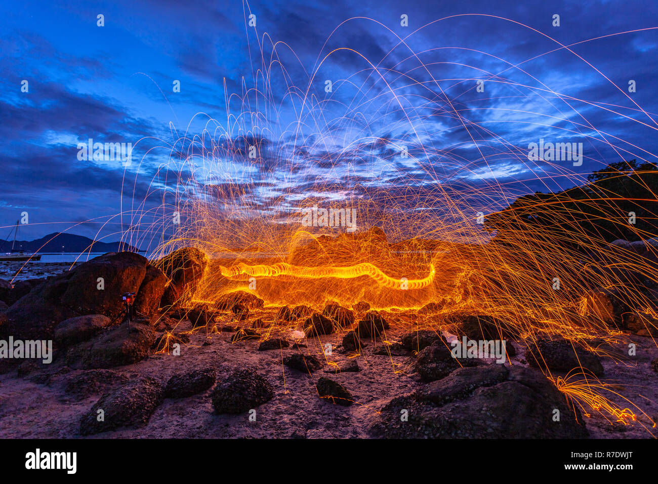 cool burning steel wool fire work photo experiments on the rock at sunrise. Stock Photo