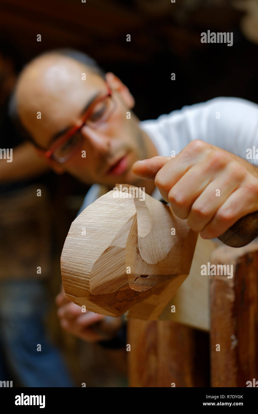 Woodworker makes traditional oarloof (forcola) for a Venetian gondola - Stock Image