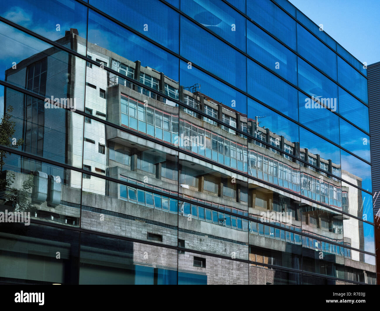 Reflection of the 1960s London Hospital Dental Institute in the modern glass of the Barts & The London School of Medicine and Dentistry in Whitechapel - Stock Image