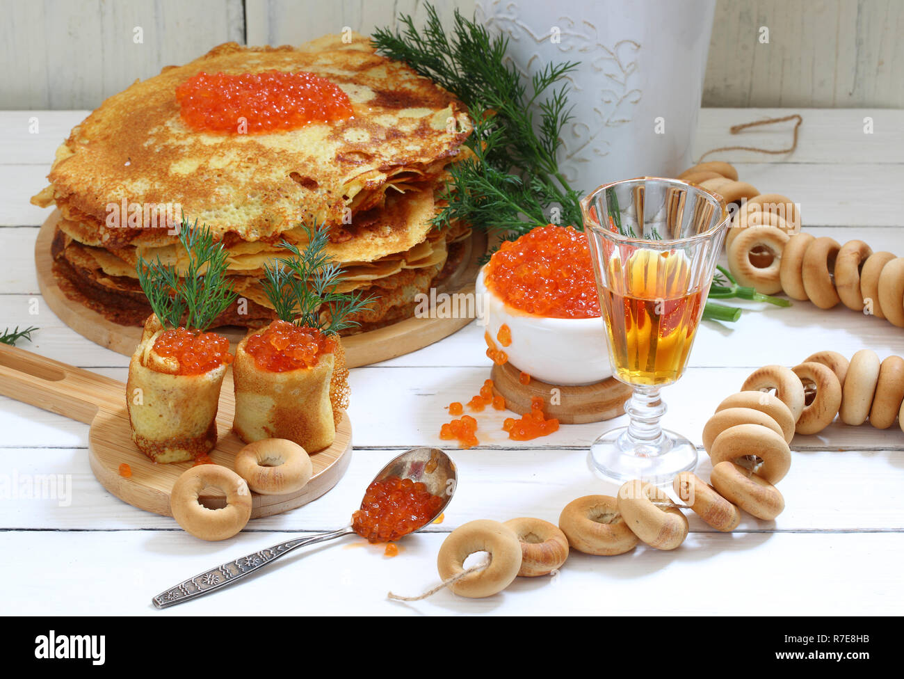 Pancakes with red caviar on a wooden table - Stock Image