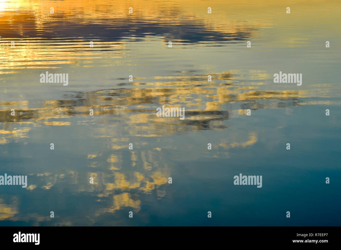 Blurred, background the surface of the water with the reflection of the evening sky. - Stock Image