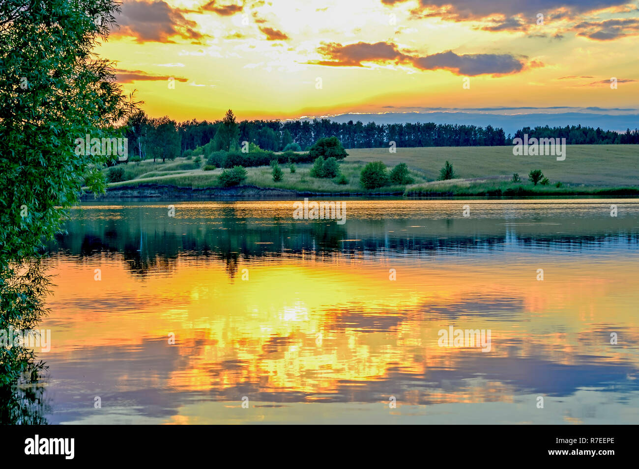 Evening landscape screensaver on the lake with the reflection in the water of the evening sky filled with sun. Background. Stock Photo