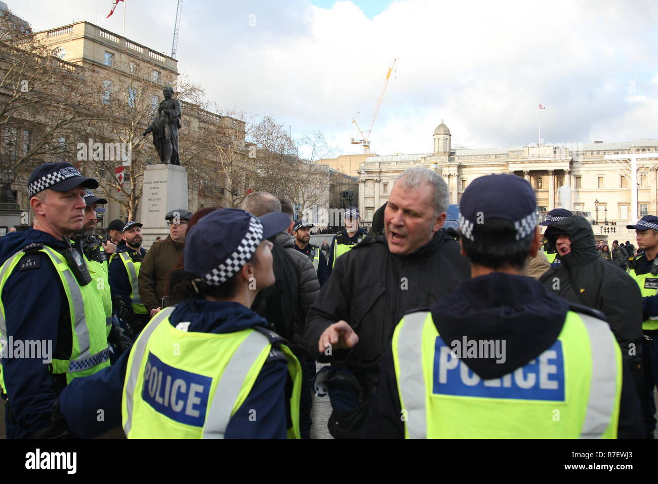 London, UK, 9th December 2018. A demonstration that organisers described as being for all anti-fascists, regardless of their positions on leave/remain on Brexit, opposes 'Tommy Robinson, fascism and racism.   The march from the BBC, Portland Place to Whitehall is a counter protest against one called by Robinson and UKIP pictured is one of Robinson's supporters arguing with a police officer after being prevented from getting near the anti racist protester.. Roland Ravenhill / Alamy Live News - Stock Image