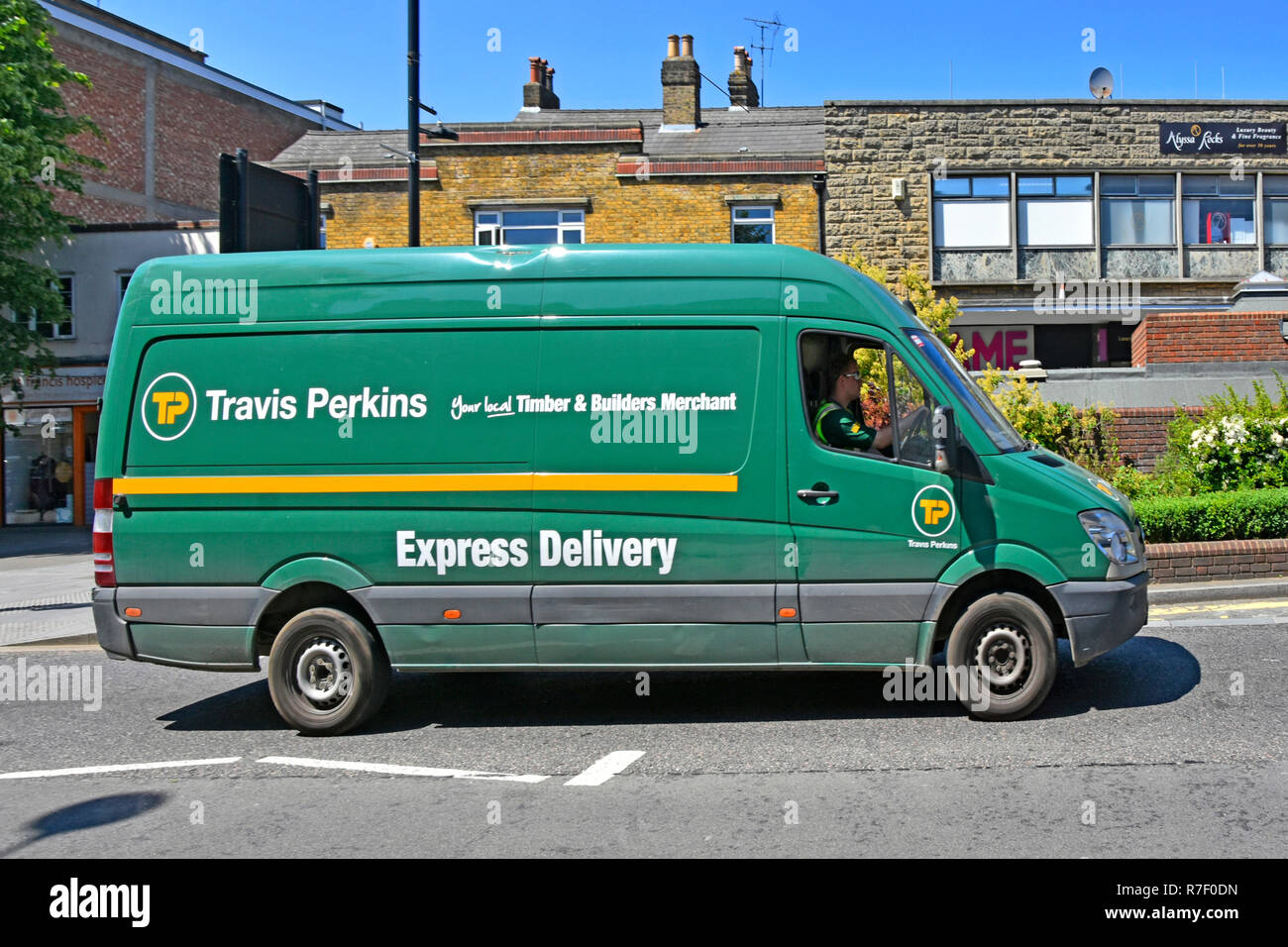 Travis Perkins builders merchants building materials supply chain business local express delivery van & driver Brentwood high street Essex England UK - Stock Image
