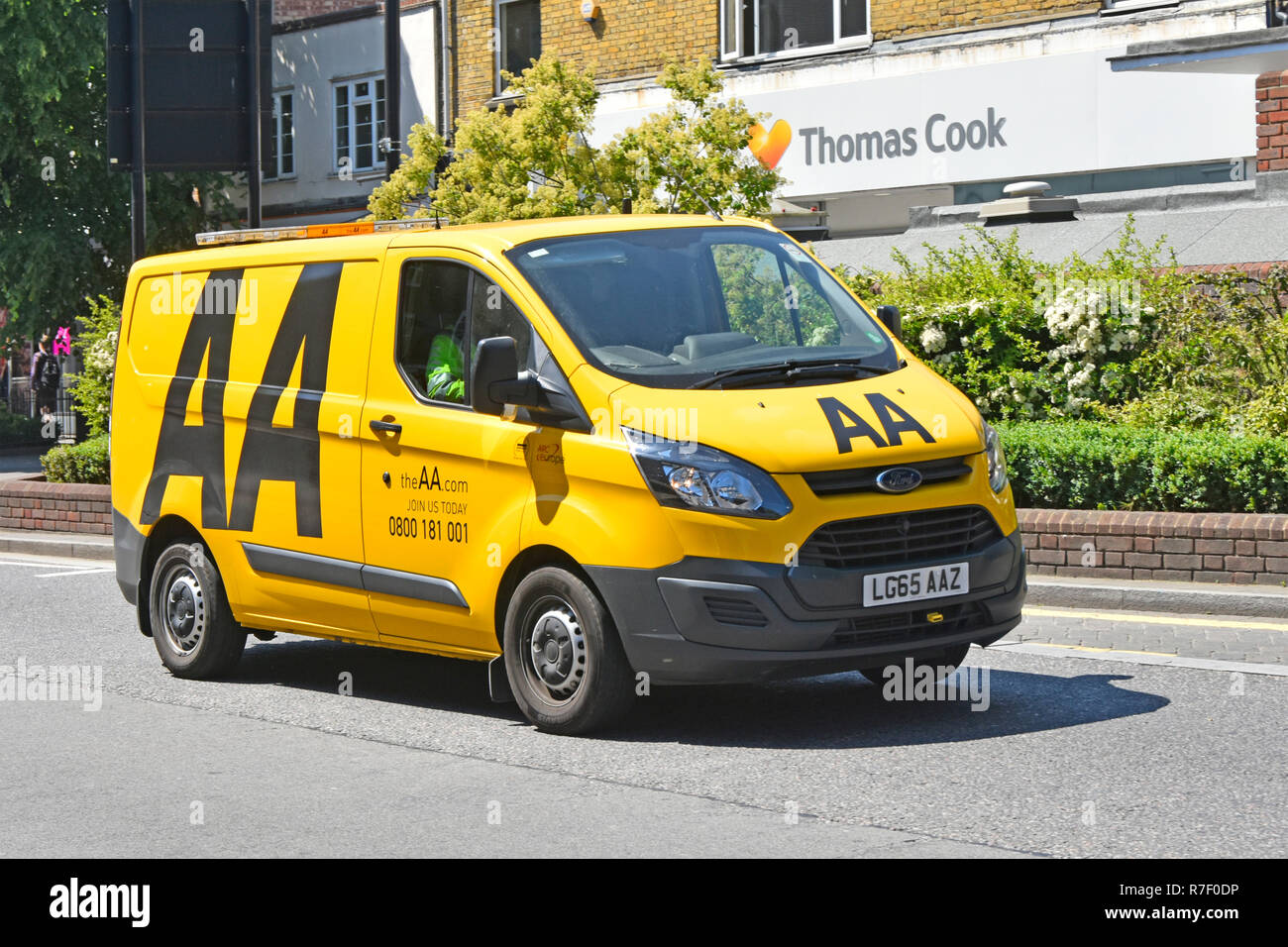 Ford Transit AA van & driver with logo on yellow breakdown van driving along town centre shopping high street in Brentwood Essex England UK - Stock Image