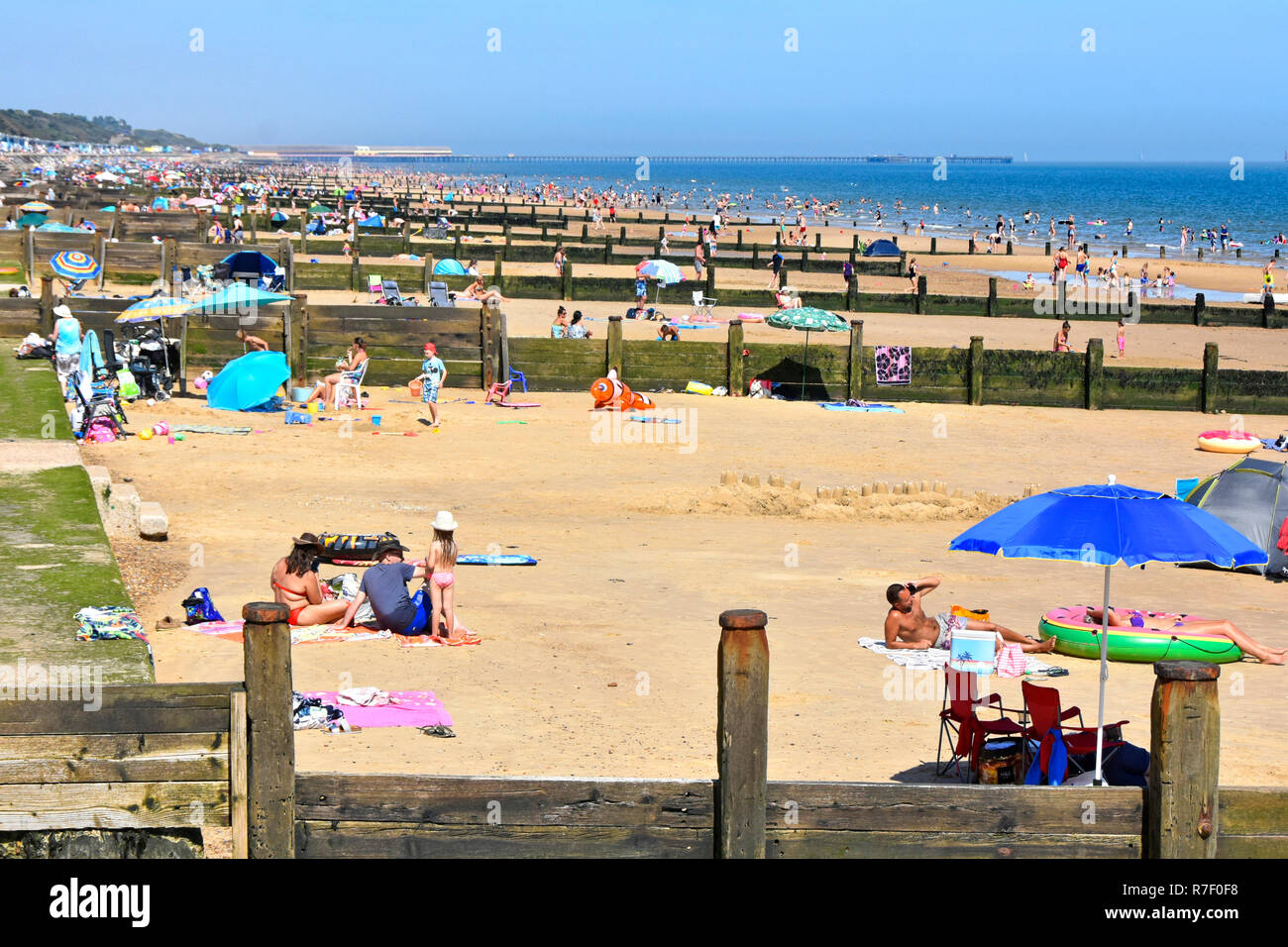 2018 hot weather summer crowds of holiday people on Essex seaside sand coast family beach for safe play & sunbathing Frinton on Sea resort England UK Stock Photo