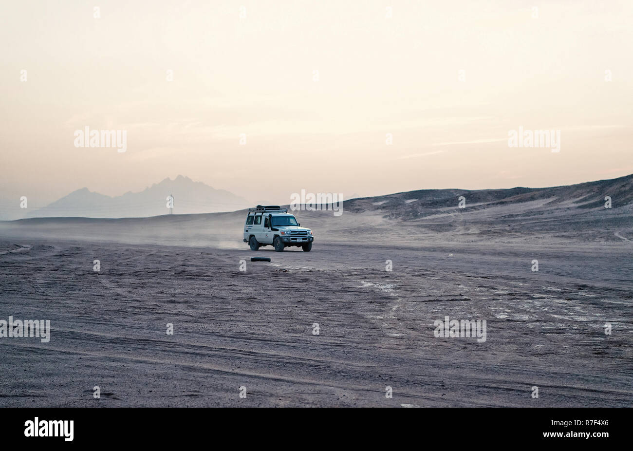 Hurghada, Egypt - February 26, 2017: car or jeep, offroad vehicle, driving in desert, sand dunes surface on white sky background. Safari and adventure. Travel, travelling. Arid landscape Wanderlust - Stock Image