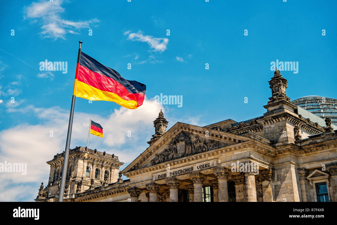 German flags waving in the wind at famous Reichstag building, seat of the German Parliament Deutscher Bundestag , on a sunny day with blue sky and clouds, central Berlin Mitte district, Germany - Stock Image