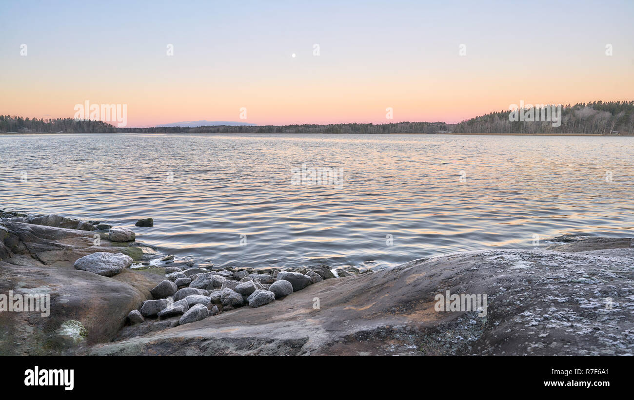 Sunrising and moonsetting by the lake - Stock Image
