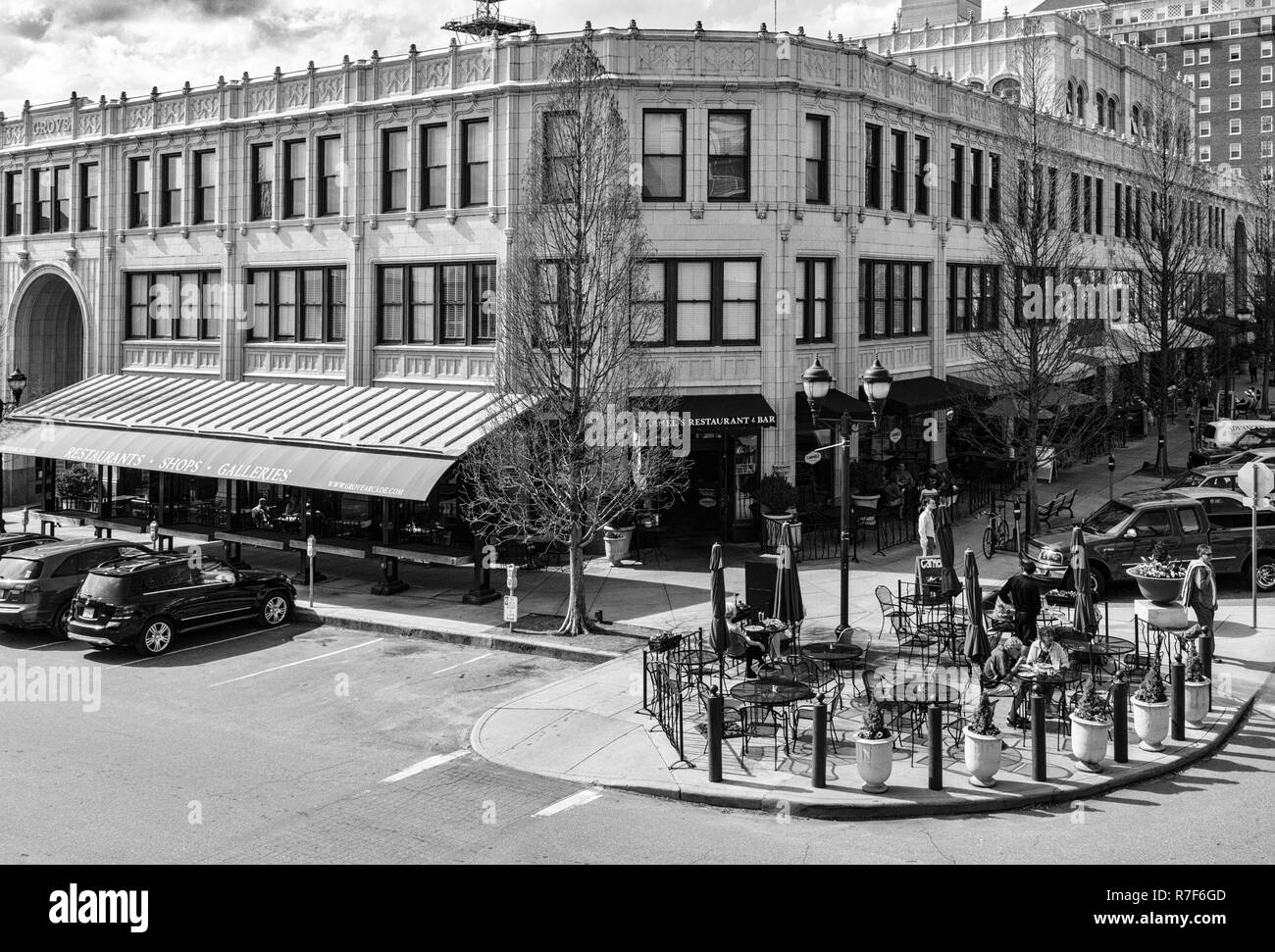Tourists walk in front of The Grove Arcade in the Downtown Asheville Historic District, the Battery Park Apartments building seen behind it. - Stock Image