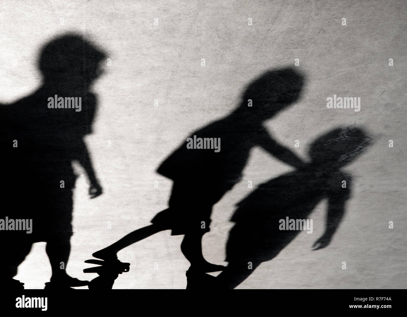 Blurry shadows of three boys friends walking together - Stock Image