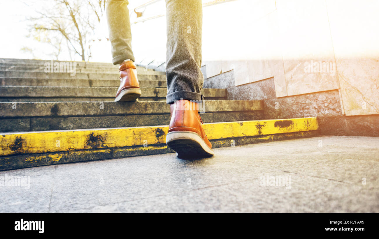 Man in beautiful brown leather shoes walks the granite stairs in an urban environment. Blank background. Life in motion concept Stock Photo