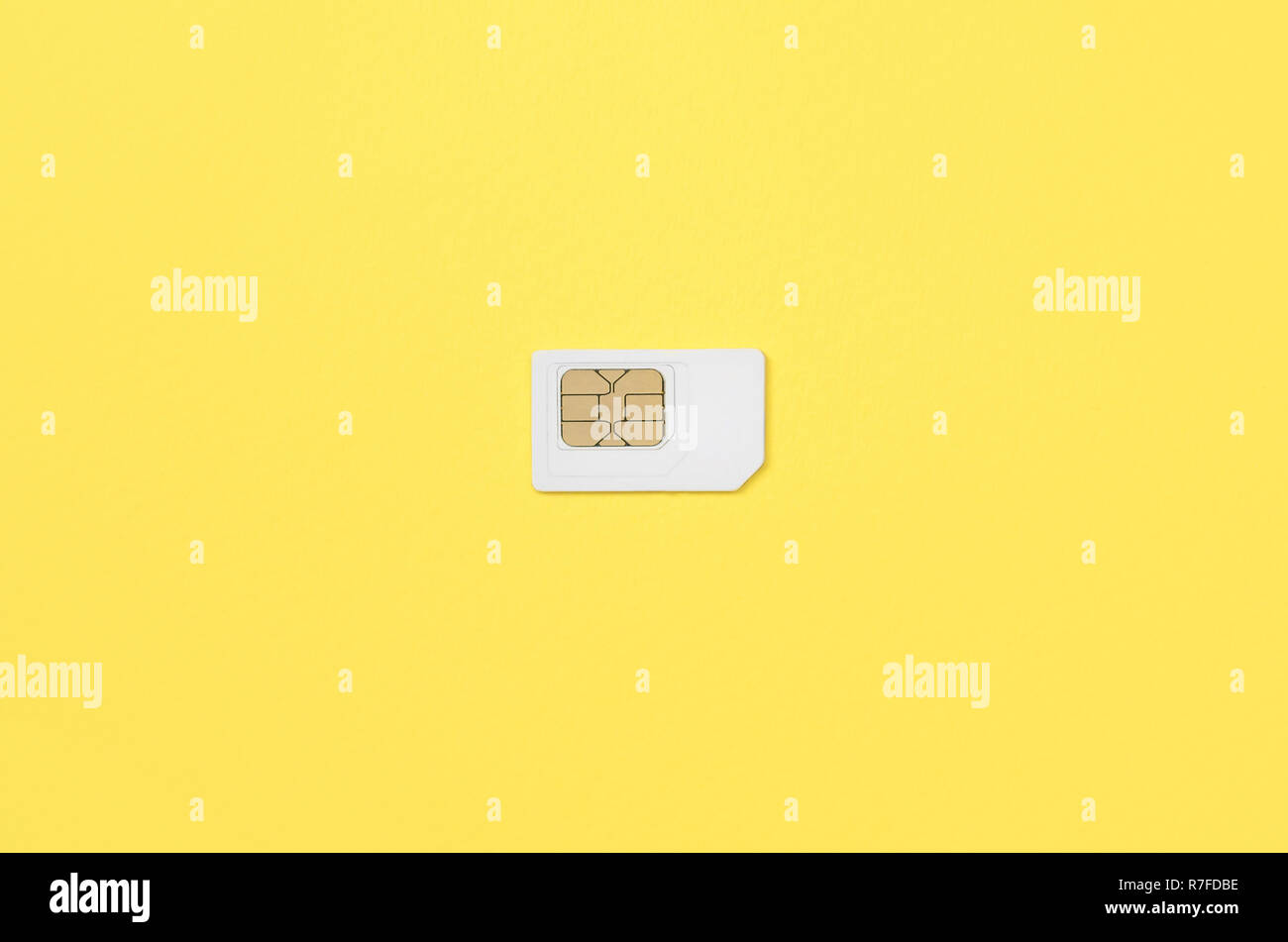 Subscriber identity module. New white SIM card on bright yellow color background. Minimal flat lay top view - Stock Image