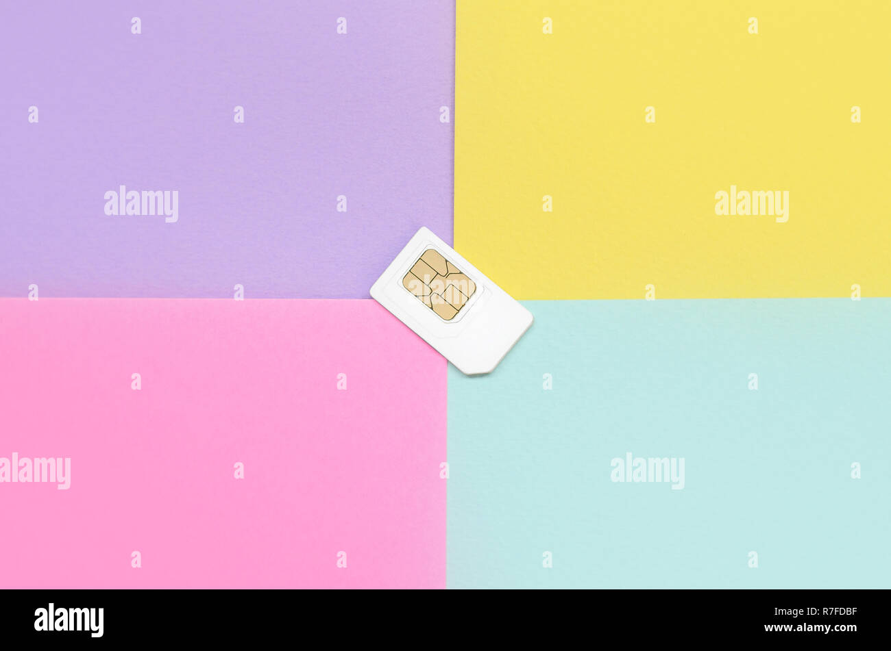 Subscriber identity module. New white SIM card on bright multicolor background. Minimal flat lay top view. Violet, pink, yellow and blue pastel colors - Stock Image