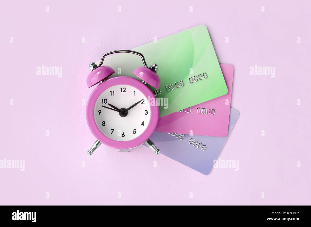 Small pink alarm clock lies on colored credit cards. The concept of modern fast online banking and funds transfer operations - Stock Image