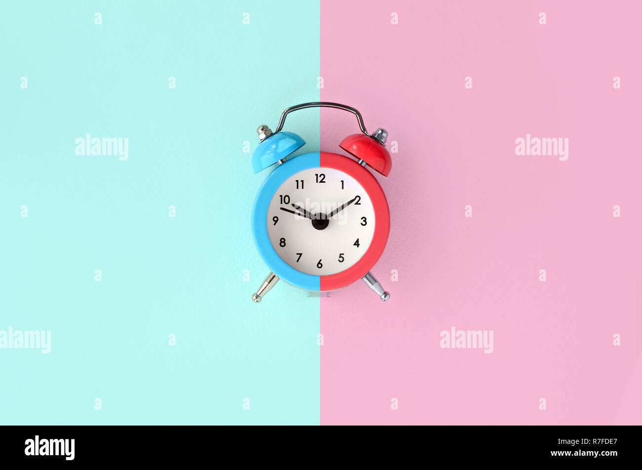 The time is at the turn of the deadline. A small color alarm clock is located between the blue and red background areas. Flat lay minimal top view - Stock Image