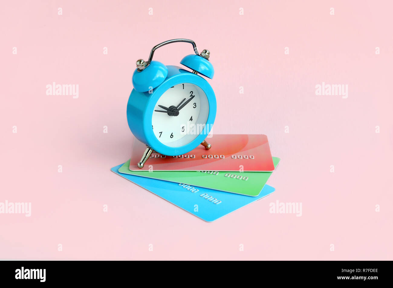 Small blue alarm clock lies on colored credit cards. The concept of modern fast online banking and funds transfer operations - Stock Image