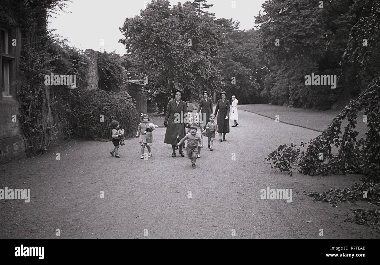 evacuated children from London with nurses on a driveway of a large country house - Stock Image