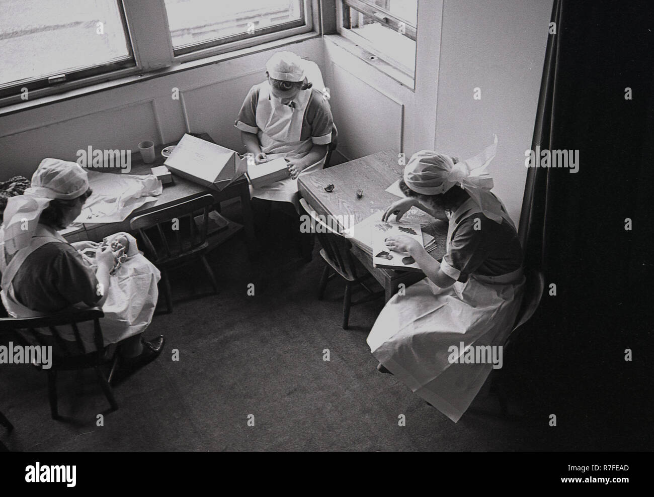 staff nurses  of a large country house preparing activities and toys for evacuated children. Stock Photo