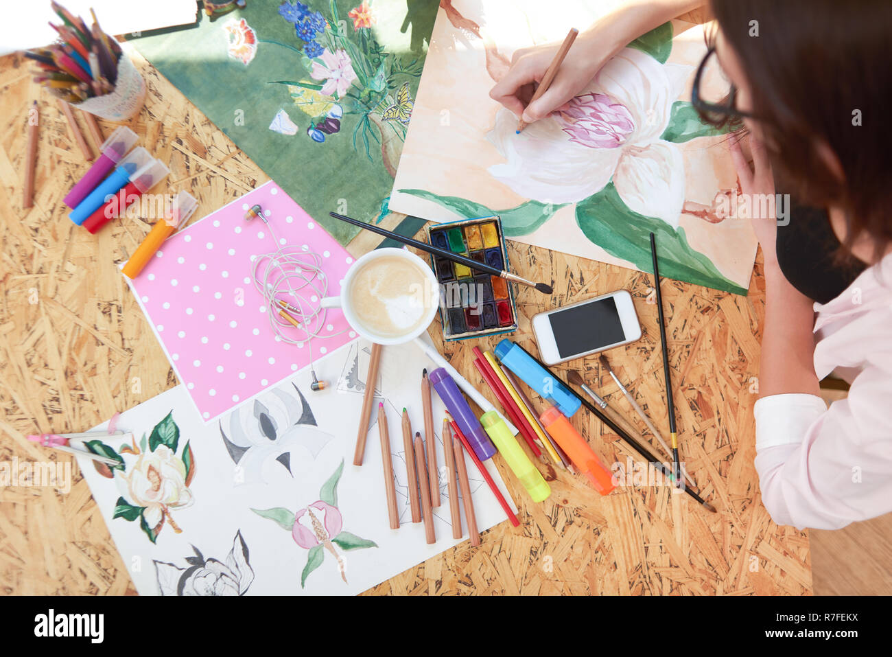 View from above of painter drawing lovely flower with pencil in hand. Different objects as containers with pencils, markers, brushes, sheets of paper, gadget and cup of coffee on table. - Stock Image