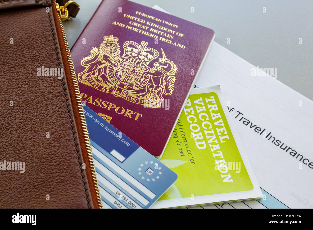 Essential travel documents for travelling abroad British biometric passport EHIC card vaccination record and travel insurance with a wallet England UK - Stock Image