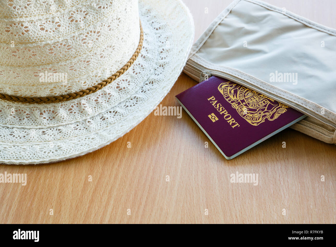 Travel things for travelling abroad British biometric passport in a wallet with lady's sunhat on a table top. England, UK, Britain - Stock Image
