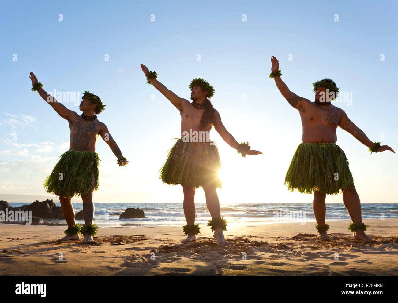 Three male hula dancers at sunset at Maui, Hawaii. - Stock Image