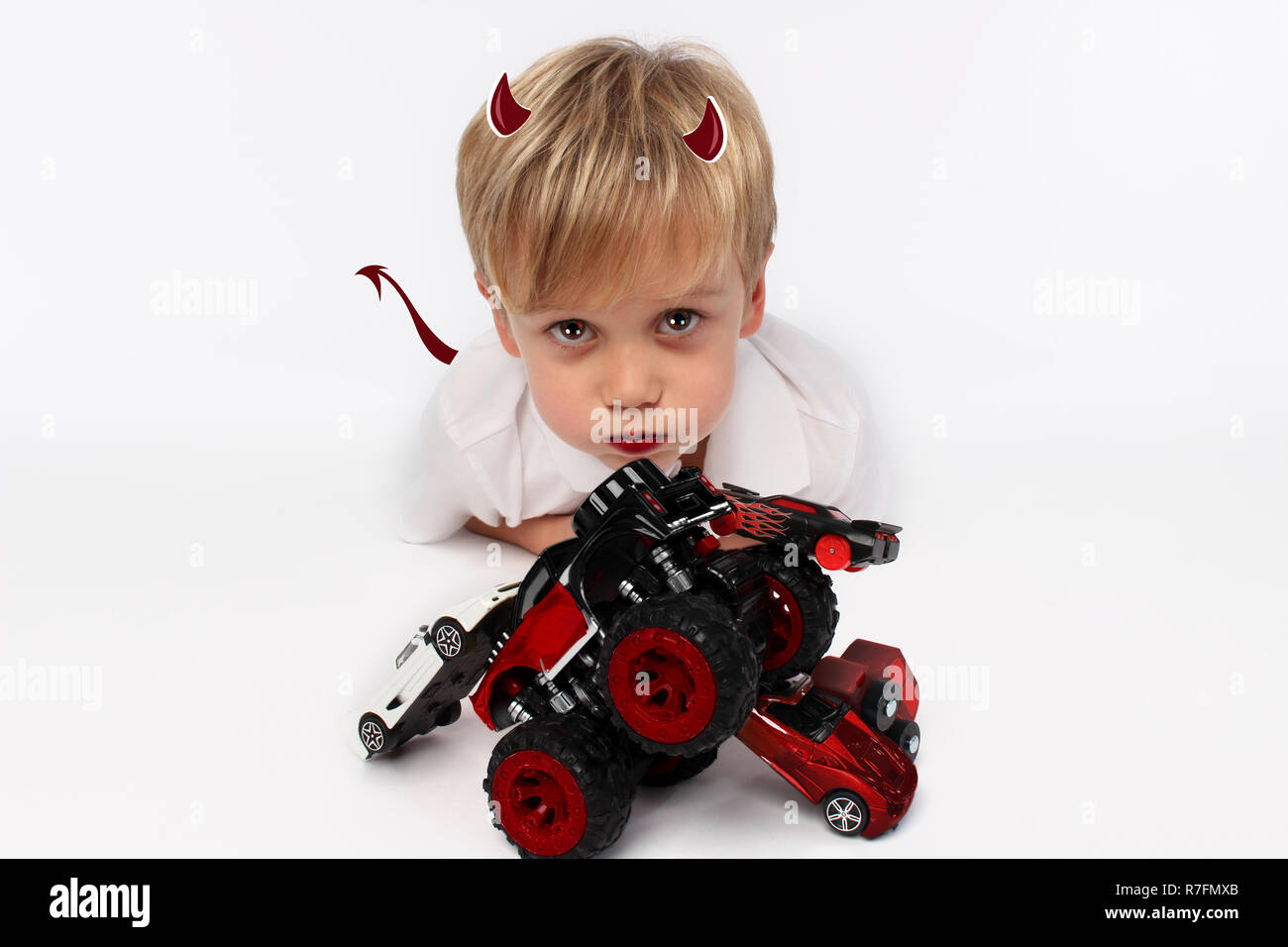 Naughty or good child for Christmas? PF or letter to Santa-Claus for Christmas. Little child boy appearing as an adorable angelic devil - Stock Image